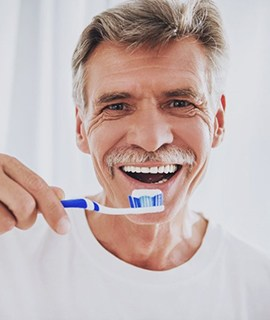 older man in white t-shirt brushing his teeth