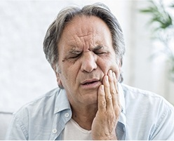 Older man in pain holding cheek