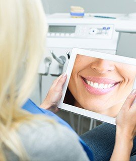Woman looking at her smile enhancement with smile design software