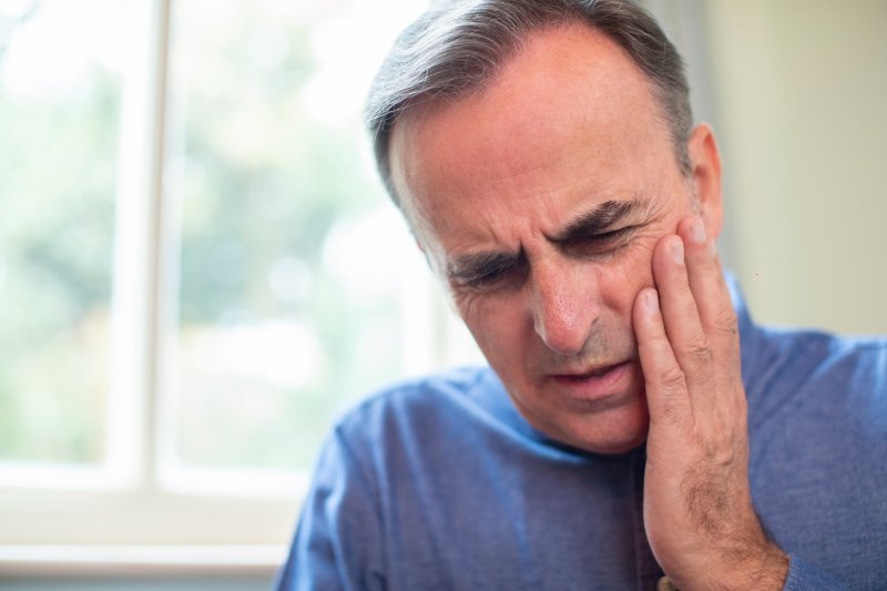 an older man dealing with dental pain