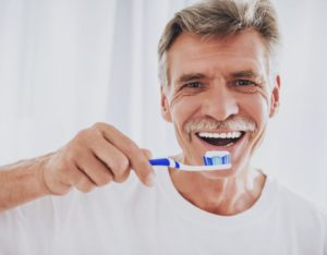 older man practicing dental implant aftercare by brushing his teeth