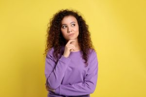 Woman standing in front of yellow background wearing a purple sweatshirt with her finger to her chin