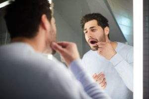 man looking in the mirror for cavities between teeth in Round Rock