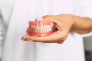 dentist holding a set of full dentures in Round Rock, TX